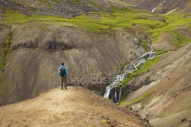 Turista che cerca al ruscello e cascate in valle rocciosa in Islanda — Foto stock