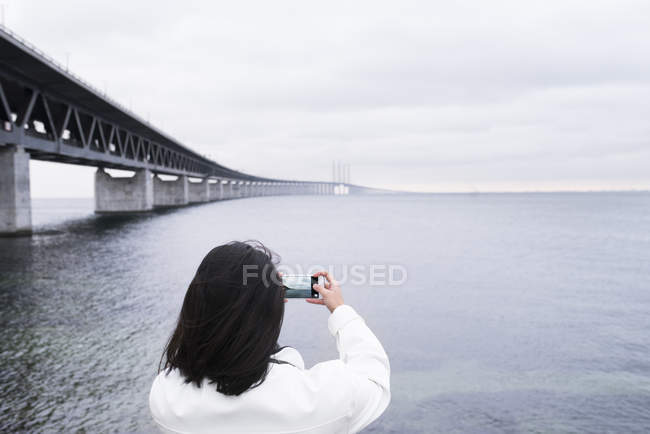 Woman photographing sea next to bridge — Stock Photo