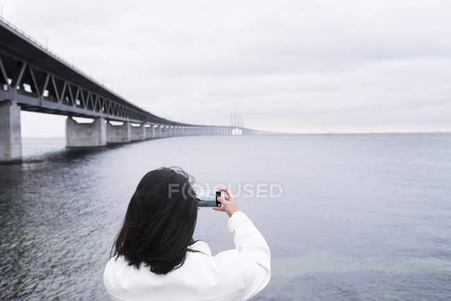 Жінка фотографує море поруч з мостом — стокове фото