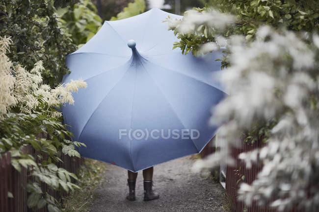 Femme avec parasol marchant dans le jardin — Photo de stock