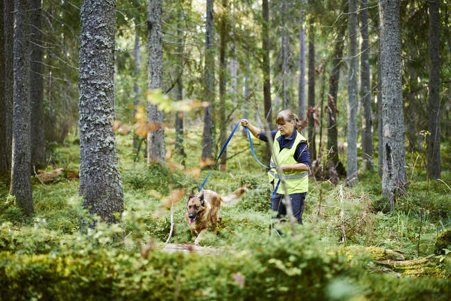 Voluntário com cão ajudando serviços de emergência encontrar pessoas desaparecidas — Fotografia de Stock