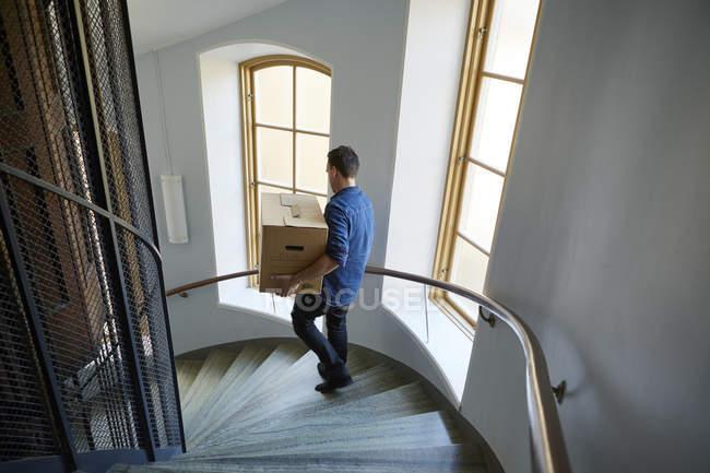 Vista de ángulo alto del hombre caminando en pasos y caja que lleva - foto de stock