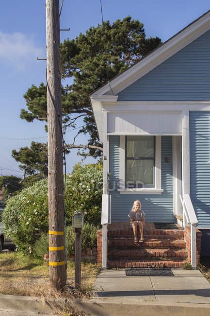 Menina sentada em degraus na frente da casa azul em Pacific Grove — Fotografia de Stock