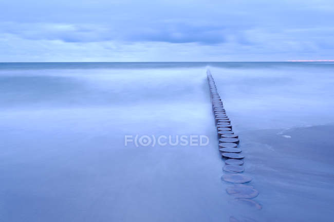 Seascape with breakwater under moody sky — Stock Photo