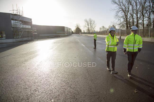 Reife Männer tragen Schutzkleidung in der Straße vor Baustelle — Stockfoto