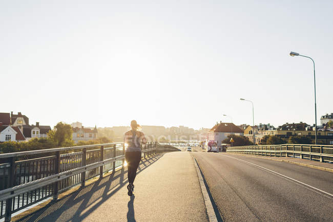 Rear view of young woman jogging on bridge — Stock Photo