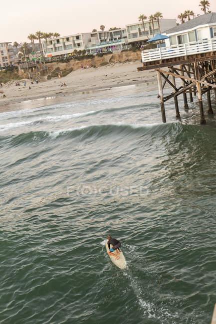 Surfeur sur l'eau à San Diego avec jetée et maisons sur la plage en arrière-plan — Photo de stock
