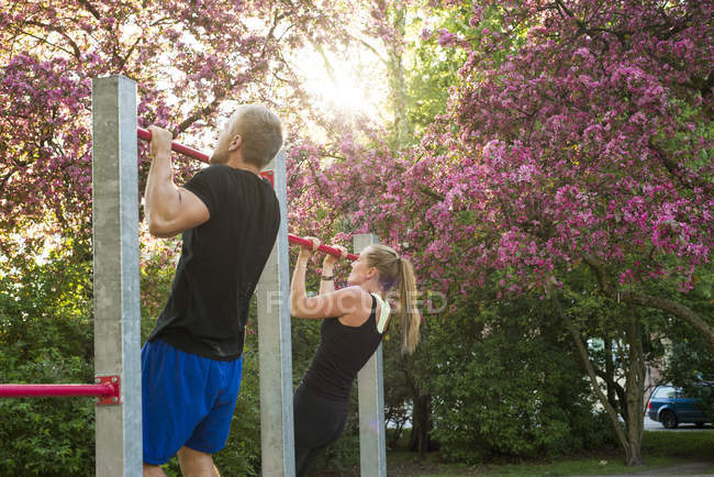 Woman and man hanging on gymnastic bar in park — Stock Photo