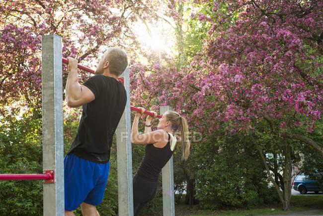 Frau und Mann hängen, gymnastische Bar im park — Stockfoto
