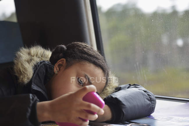 Fille assise dans le train et à l'aide de smartphone — Photo de stock