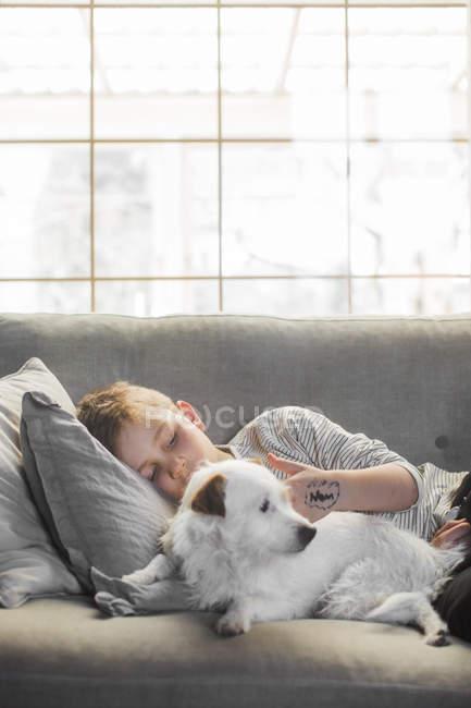 Menino deitado no sofá com o cachorro perto de janela — Fotografia de Stock