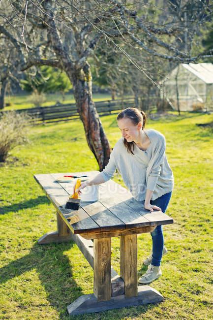 Mitte Erwachsene Frau Ölen Holztisch im Garten — Stockfoto