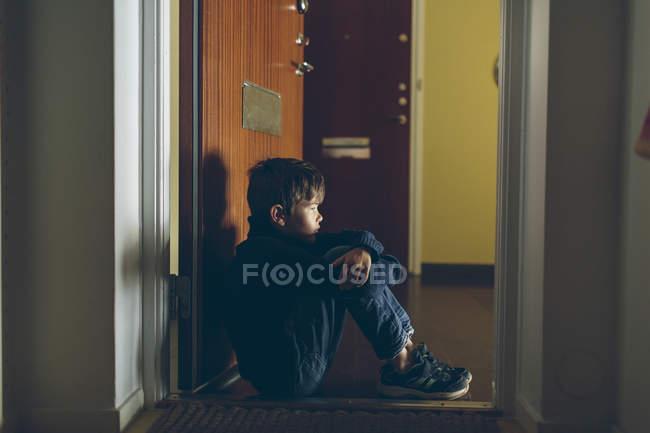Boy sitting on floor next to door, differential focus — Stock Photo