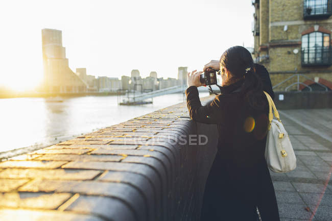 Взрослая женщина фотографирует на берегу реки в Ротерхите — стоковое фото