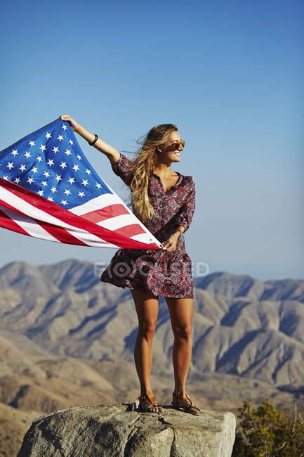 Молодая блондинка женщина, держащая нас флаг перед горный пейзаж — стоковое фото