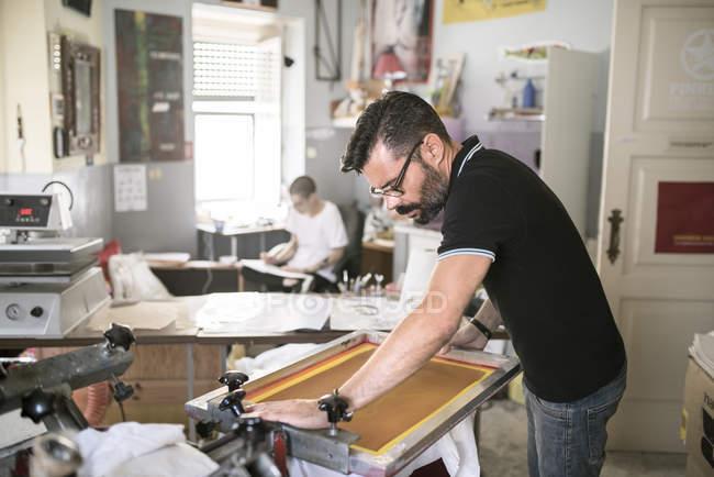 Mature man operating screen printing equipment — Stock Photo