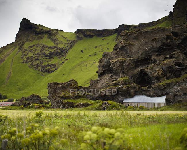 Cabanas construídas na encosta da montanha no vale verde exuberante, Islândia — Fotografia de Stock