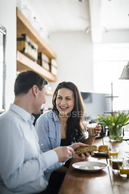 Пара во время завтрака, фокус на фоне — стоковое фото