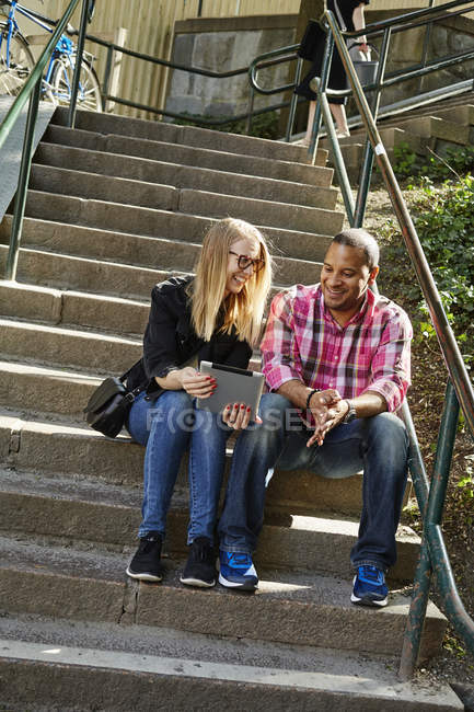 Man and woman sitting side by side on steps and looking at digital tablet — Stock Photo