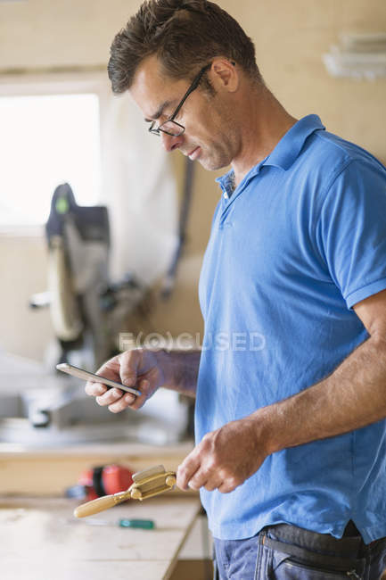 Carpenter using phone in workshop, focus on foreground — Stock Photo