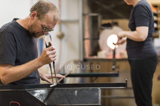 Man and woman working in workshop, focus on foreground — Stock Photo