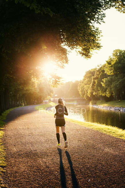 Jogger running down alley along canal in park — Stock Photo