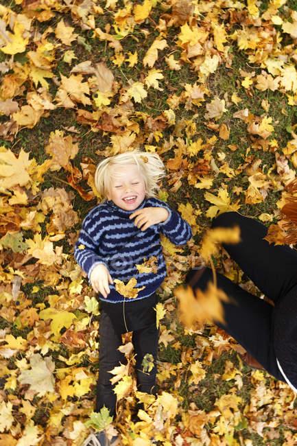 Блондинка хлопчик лежачи і сміючись в Осіннє листя поблизу жінка — стокове фото