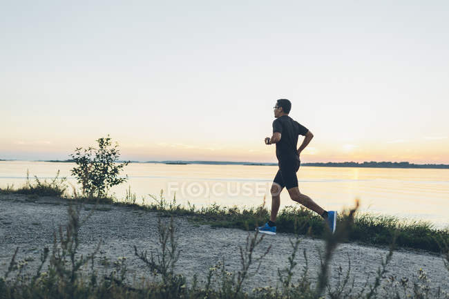 Side view of mid adult man jogging at seashore — Stock Photo