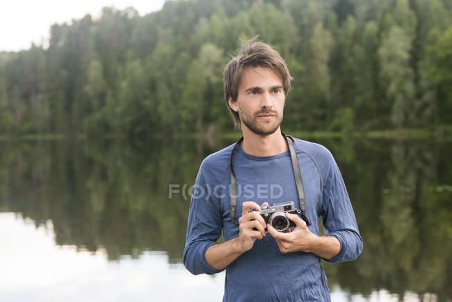 Junger Mann mit Kamera am Seeufer mit Wald im Hintergrund — Stockfoto