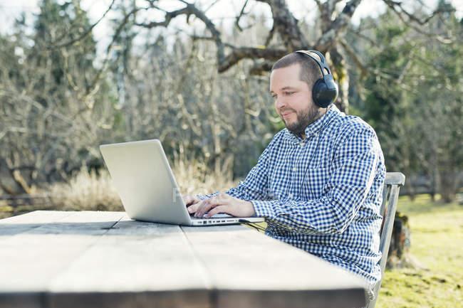 Homme adulte moyen utilisant un ordinateur portable dans le jardin — Photo de stock