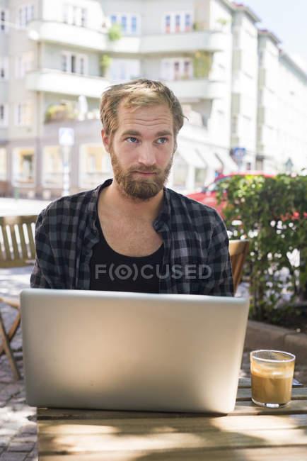 Man using laptop on summer terrace, focus on foreground — Stock Photo
