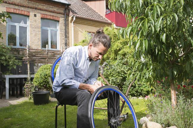 Mann Befestigung Fahrrad gegen Gebäude außen — Stockfoto