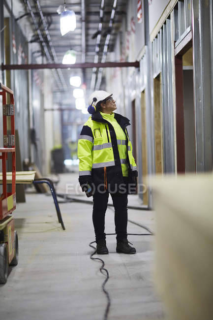 Woman in protective clothing standing and looking away — Stock Photo