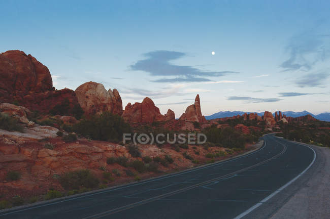 Road stretching beside rock formations in Arches National Park — Stock Photo