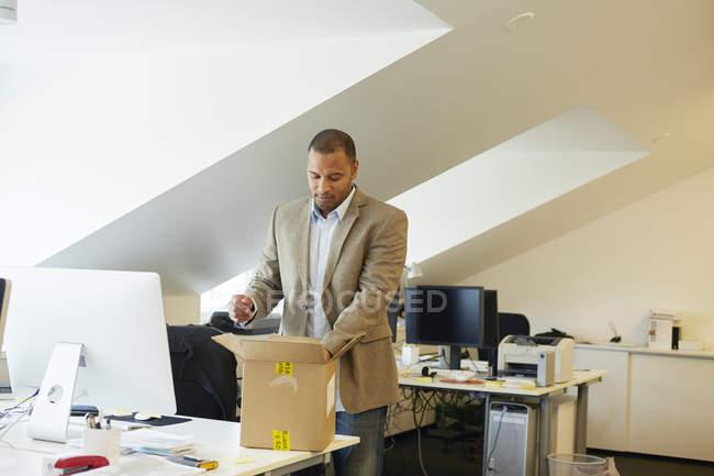 Бізнесмен відкриття пакету в офісі і, дивлячись — стокове фото