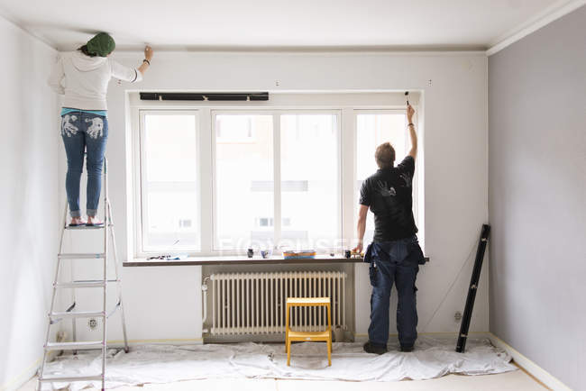 Rear view of couple painting wall of room — Stock Photo