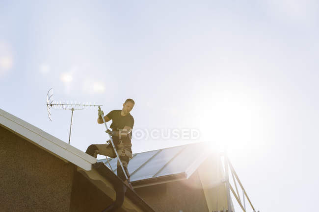 Man in protective workwear painting roof — Stock Photo