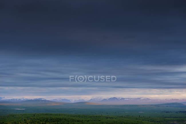 Vista del paisaje de la cordillera en el horizonte y el cielo malhumorado - foto de stock