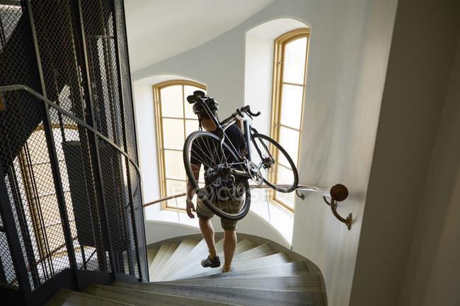Vista de ángulo alto de ciclista llevar bicicleta en pasos - foto de stock