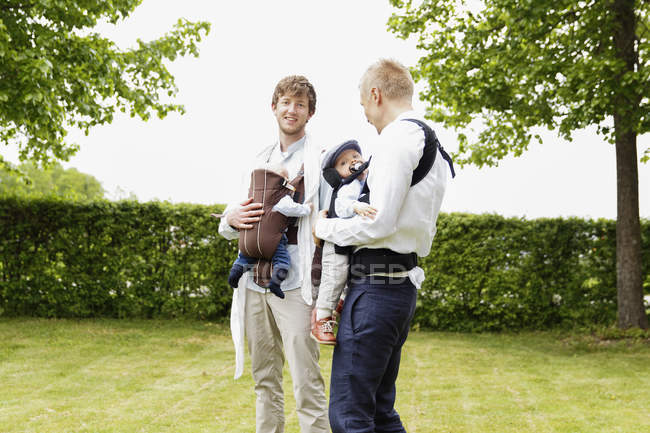 Two fathers holding baby boys in garden — Stock Photo