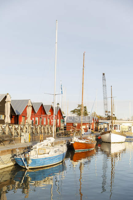 Fishing houses and old sailboats on riverbank in sunlight — Stock Photo
