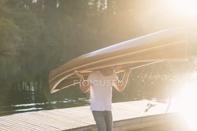 Man carrying wooden rowboat on head, lens flare — Stock Photo