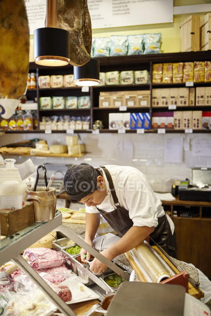 Young man working in store, focus on foreground — Stock Photo