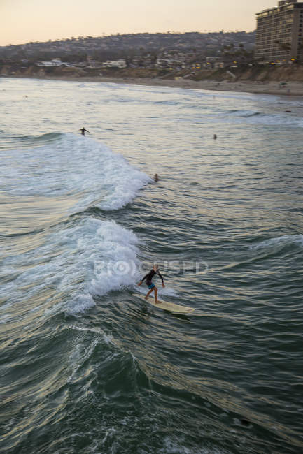 Surfer on water in San Diego with beach and city in background — Stock Photo