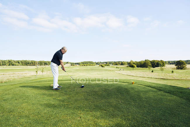 Вид сбоку на пожилого человека, играющего в гольф — стоковое фото