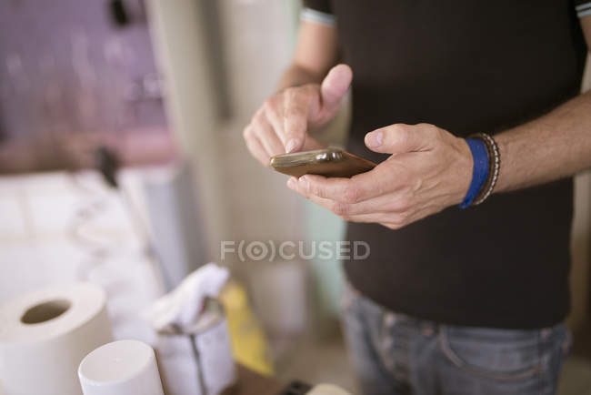 Man using cell phone, focus on foreground — Stock Photo