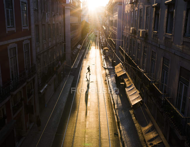 Silhouette of pedestrian crossing empty street in Portugal — Stock Photo