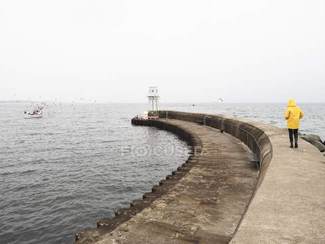 Man wearing raincoat walking on pier — Stock Photo
