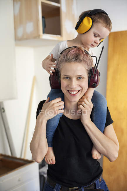 Mid adult woman carpenter carrying son on shoulders — Stock Photo