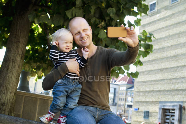 Отец и маленький сын фотографируют себя со смартфона — стоковое фото